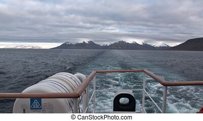 Back of the ship in water of Arctic Ocean on background of mountain in Svalbard.