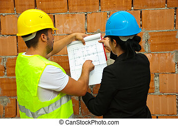 Back of two architects with blueprints on site