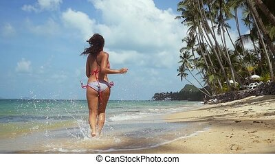 Back of view of pretty young brunette woman in bikini running along the exotic sandy beach on sunny summer day. slow motion. 1920x1080