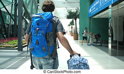 Back of view of young man with backpack pulling suitcase in modern airport terminal. Travelling handsome guy walking away with his luggage