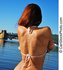 Back of woman dipping into the river
