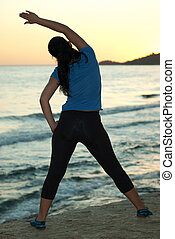 Back of woman doing fitness at sunset