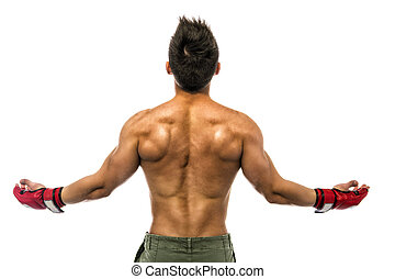 Back of young bodybuilder wearing MMA gloves, with arms spread open