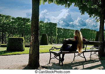 Back of young woman relaxing in park