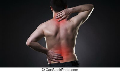 Back pain, man with backache on black background