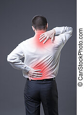 Back pain, man with backache on gray background