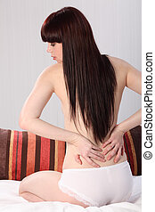 Back pain woman examines herself with both hands - Beautiful...