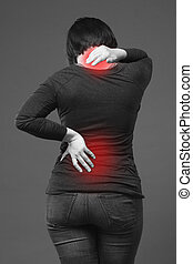 Back pain, woman with backache on gray background