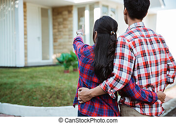 young couple standing in front of their new house