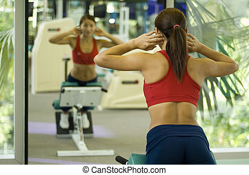 A female fitness instructor demonstrates a back raise in a mirror