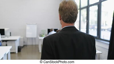 Back Rear View Of Serious Businessman Walking Through Modern Office Looking At Business People Staff Work On Computers