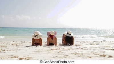 Back Rear View Of Three Girls Lying On Beach Raising Legs, Enjoy Sun Tan, Woman Tourists On Summer Holiday