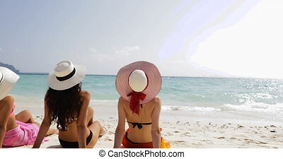 Back Rear View Of Three Girls On Beach In Bikini And Straw Hats Enjoy Sun Tan Talking, Woman Tourists On Summer Holiday