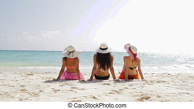 Back Rear View Of Three Girls On Beach In Bikini And Straw Hats Enjoy Sun Tan, Woman Tourists Group On Summer Holiday