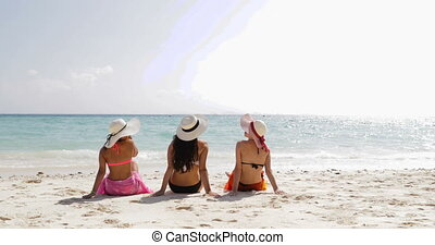 Back Rear View Of Three Girls On Beach In Bikini, Enjoy Sun Tan Talking, Woman Taking Off Straw Hats Tourists On Summer Holiday