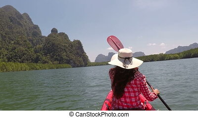 Back Rear View Of Woman Kayaking In Beautiful Lagoon Action...