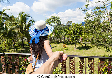 Back Rear View Of Young Woman In Hat Over Beautiful Tropical Landscape Holding Man Hand