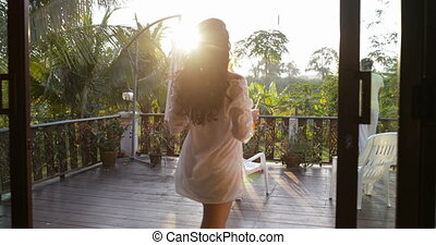 Back Rear View Of Young Woman Walk On Summer Terrace With Juice To Man Looking At Sunset Landscape Over Tropical Forest