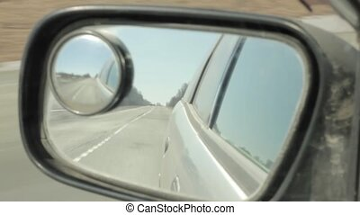 Back road reflected in car mirror, car driving fast on a motorway