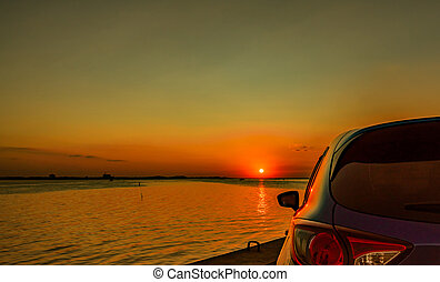 Back scene of blue compact SUV car with sport and modern design parked on concrete road by the sea at sunset. Environmentally friendly technology. Business success concept.