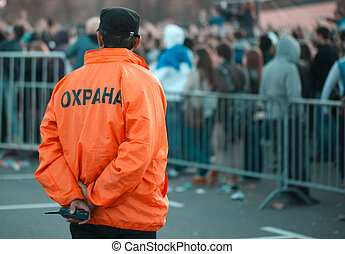 Back security guard in front of blurred crowd