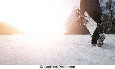 Back Shot of Walking Snowboarder Holding Snowboard - Back...