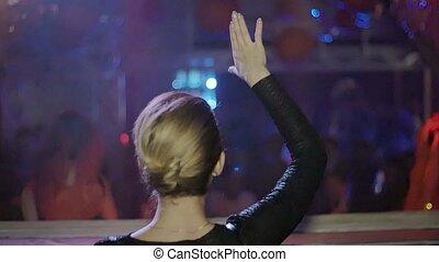 Back side Dj girl dance at turntable in nightclub. Go go girls. Slow motion