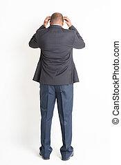 Back side full length mature Indian businessman thinking -...
