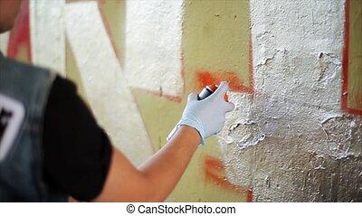 Back side graffiti artist paint spraying the wall. Summer...