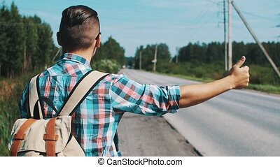 Back side of young boy stay with backpack thump up at road in summer sunny day. Hitchhiking