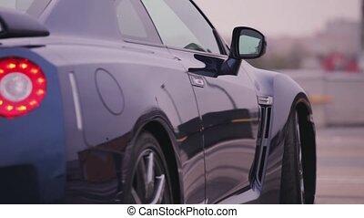 Back side of dark blue new car. Wheels. Presentation.  Red lights. Bumper. Automobile. Cold shades
