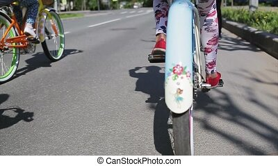 Back side of girl cycling with other people, wheel focus in out. Slow motion.