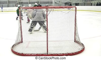 Back side of hockey goalkeeper in a moment of a game on ice rink. Slow motion.