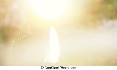 Back side of silhouette man in sun beams singing at microphone on stage. Live concert. Singer