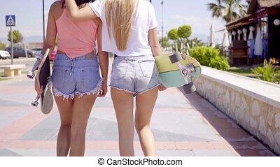 Back side of two girls in short jeans and backward hats walking with skateboards on sidewalk