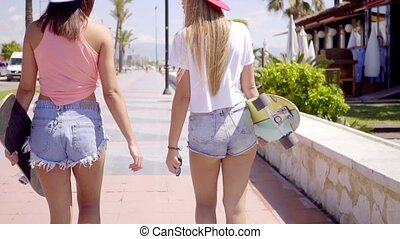 Back side of two girls with skateboards