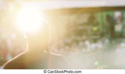 Back side silhouette man in sun beams perform in microphone on stage. Live concert. Crowd of people
