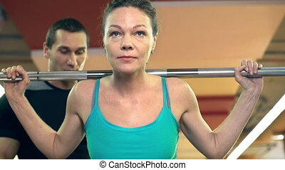 Back Squat - Close up of woman doing barbell back squat...