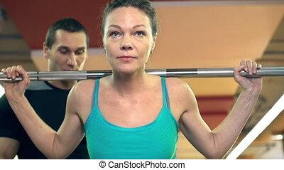 Back Squat - Close up of woman doing barbell back squat...