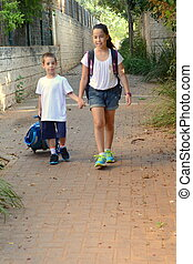 Back to school: a teenaged sister accompanying her first-grader little brother on the first day of school