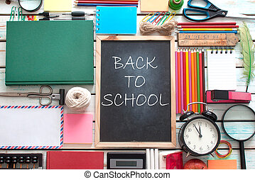 Aerial view of stationery objects with back to school written on blackboard