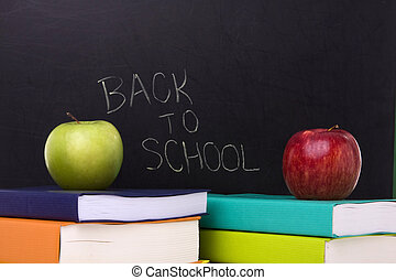 Back to school - apple over a stack of books next to a...