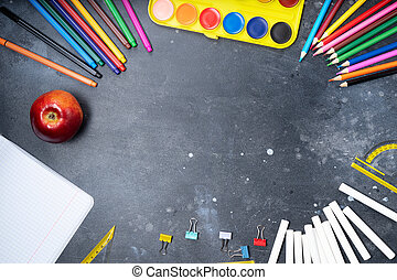 Back to school concept, frame with colorful school supplies on blackboard background with copy space