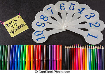 "Back to school background with a lot of colorful felt-tip pens and colorful pencils, cards of numerals from one to ten and title ""Back to school"" written on the yellow piece of paper on the chalkboard"
