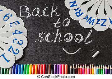 "Back to school background with a lot of colorful felt-tip pens and colorful pencils, cards of numerals from one to ten and title ""Back to school"" written by chalk on the chalkboard"