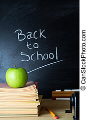 Back to School Blackboard - Teacher's desk with a pile of...