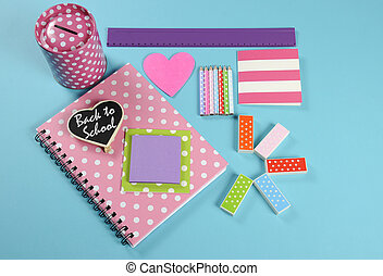 Back to School bright pink, polka dot and colorful stationery and office supplies with money savings box on pale blue background.