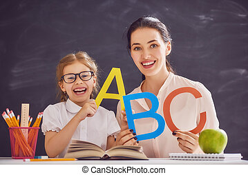 woman teaches child the alphabet - Back to school! Child is ...