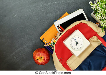 Back to school concept. Backpack with school supplies, clock, tablet and apple against chalk board. Top view. Copy space