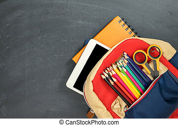 Back to school concept. Backpack with school supplies, tablet and against chalk board. Top view. Copy space